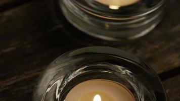 Velas de té con mechas en llamas sobre un fondo de madera - velas 004