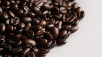 rotierender Schuss von köstlichen, gerösteten Kaffeebohnen auf einer weißen Oberfläche - Kaffeebohnen 068