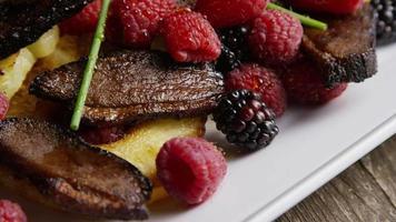 tomada rotativa de um delicioso prato de bacon de pato defumado com abacaxi grelhado, framboesas, amoras e mel - comida 105 video