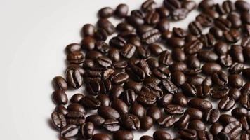 colpo rotante di deliziosi chicchi di caffè tostati su una superficie bianca - chicchi di caffè 039