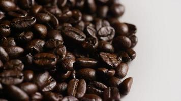 Tiro giratório de grãos de café torrados deliciosos em uma superfície branca - grãos de café 069