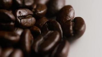 Tiro giratório de grãos de café torrados deliciosos em uma superfície branca - grãos de café 073 video