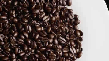 dose rotativa de deliciosos grãos de café torrados em uma superfície branca - grãos de café 055