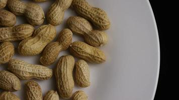 Cinematic, rotating shot of peanuts on a white surface - PEANUTS 002
