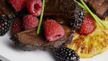 foto rotativa de um delicioso prato de bacon de pato defumado com abacaxi grelhado, framboesas, amoras e mel - comida 119 video
