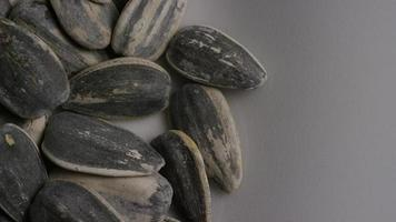 Cinematic, rotating shot of sunflower seeds on a white surface - SUNFLOWER SEEDS 006