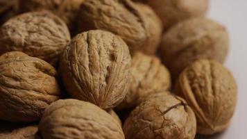 filmische, roterende opname van walnoten in hun schelp op een wit oppervlak - walnoten 074