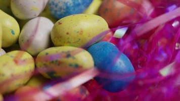 Foto giratoria de coloridos dulces de pascua sobre un lecho de pasto de pascua - pascua 141
