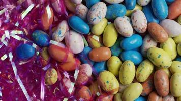 Foto giratoria de coloridos dulces de Pascua sobre un lecho de pasto de Pascua - Pascua 113
