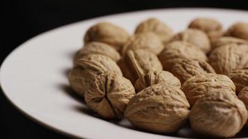 filmische, roterende opname van walnoten in hun schelpen op een wit oppervlak - walnoten 029