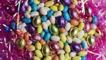 Foto giratoria de coloridos dulces de pascua sobre un lecho de pasto de pascua - pascua 157