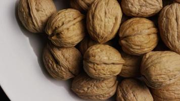 Cinematic, rotating shot of walnuts in their shells on a white surface - WALNUTS 050