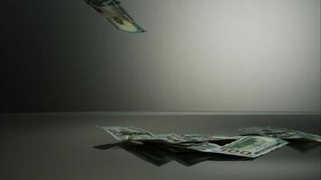notas de US $ 100 caindo em uma superfície reflexiva - dinheiro fantasma 043