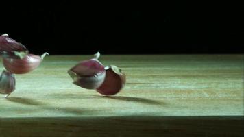 Knoblauchzehenstücke springen in Ultra-Zeitlupe (1.500 fps) auf einer Holzoberfläche - Grillphantom 027