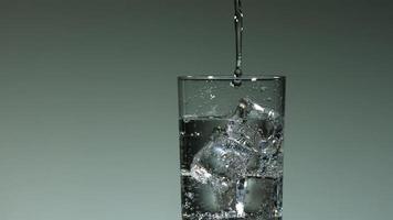 líquido transparente carbonatado que se vierte y salpica en cámara ultra lenta (1,500 fps) en un vaso lleno de hielo - líquido vertido 002