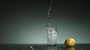 líquido transparente carbonatado que se vierte y salpica en cámara ultra lenta (1,500 fps) en un vaso lleno de hielo - líquido vertido 027