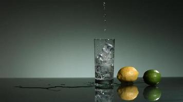 líquido transparente carbonatado que se vierte y salpica en cámara ultra lenta (1,500 fps) en un vaso lleno de hielo - líquido vertido 001