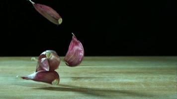 Knoblauchzehenstücke springen in Ultra-Zeitlupe (1.500 fps) auf einer Holzoberfläche - Grillphantom 031