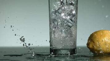 líquido transparente carbonatado que se vierte y salpica en cámara ultra lenta (1,500 fps) en un vaso lleno de hielo - líquido vertido 014