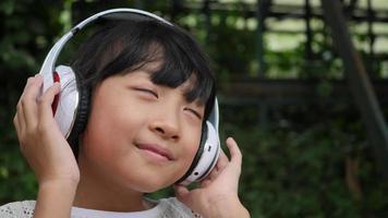 garotinha ouve música no fone de ouvido e se sentindo bem
