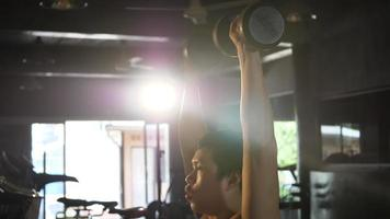 Joven mano sujetando pesas hasta ejercicios en el gimnasio fitness