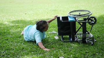 Une patiente âgée veut aider après qu'un fauteuil roulant s'est renversé dans le sol