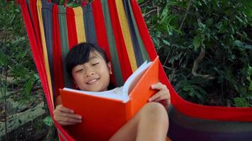 Little girl chilling on hammock and reading a book story