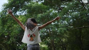 menina asiática brincando ao ar livre em câmera lenta, girando, sorrindo e levantando as mãos no ar