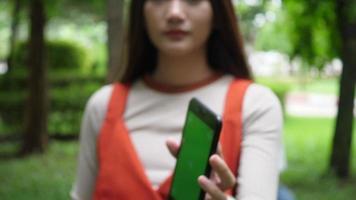 linda mulher usando smartphone e mostrando tela verde para a câmera