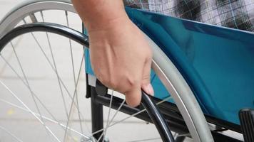 Gros plan de la main d'un patient tenant un fauteuil roulant et le conduire seul
