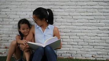 Mother and daughter read funny stories.