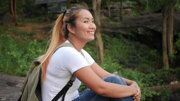 Une femme touriste assis sur un rocher lors d'une randonnée