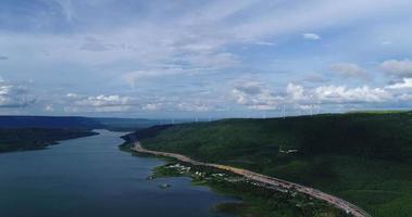 Vista aérea sobrevolando turbinas eólicas en las montañas con carretera video