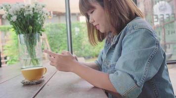 Female blogger photographing green tea cup in cafe with her phone. video