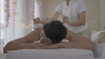 Joven recibiendo masaje de espalda del terapeuta de spa