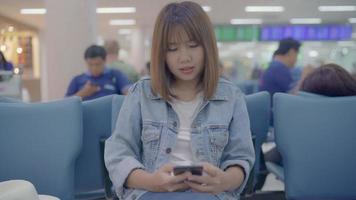 glückliche asiatische Frau, die ihr Smartphone benutzt und überprüft, während sie auf Stuhl in der Terminalhalle sitzt, während sie ihren Flug am Abfluggate im internationalen Flughafen wartet.