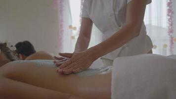 Young women receiving back massage spa therapist applying scrub salt