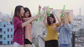 Group of young asian women people dancing and raising their arms up in air to the music played by dj at sunset urban party on rooftop. Young asian girls friends hanging out with drinks.