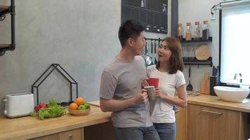 Beautiful happy asian couple are drinking a cup of coffee together in the kitchen. Man and woman talking while having breakfast. Young asian couple have romantic time while staying at home.