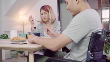 Feliz doce casal asiático homem em uma cadeira de rodas tomando café da manhã