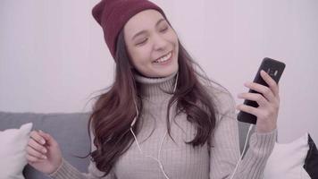 mulher asiática usa smartphone para enviar mensagens de texto, ler, enviar mensagens e comprar online enquanto está deitada no sofá da sala de estar em casa. video