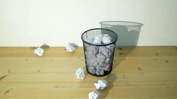 Wide shot of white crumpled paper being thrown into a trash bin