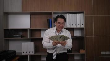 homme d'affaires prospère disperse de l'argent et célèbre en dansant au bureau