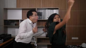 Two joyful colleagues in formal suits dancing cheerful in office
