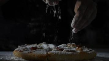 Slow motion of a woman's hands sifting flour over a pizza