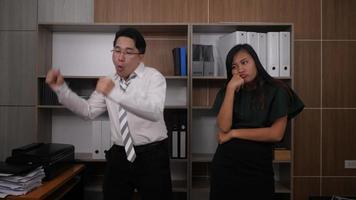 Dos colegas alegres en trajes formales bailando alegremente en la oficina.