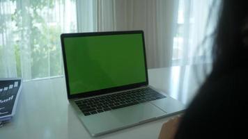 close-up das mãos de uma mulher em um laptop com espaço reservado para tela verde
