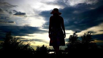 Silhouette der Frau, die ihre Hände mit der untergehenden Sonne im Hintergrund erhebt