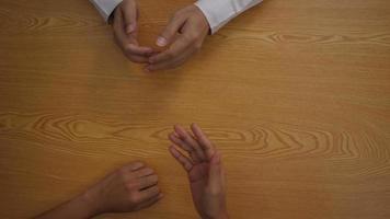 Vista superior de manos hablando sobre planes de negocios y tomando pagos.