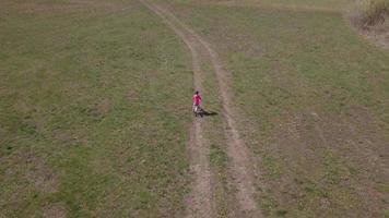 Drone follows a girl on bicycle in 4K
